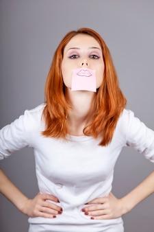 Ritratto di ragazza dai capelli rossi con adesivi divertenti colorati sulla bocca