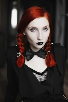 Ritratto di ragazza dai capelli rossi in farfallino su uno sfondo scuro, stile gotico