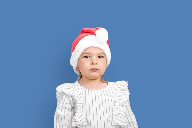 Ritratto di ragazza del bambino in cappello rosso a natale.