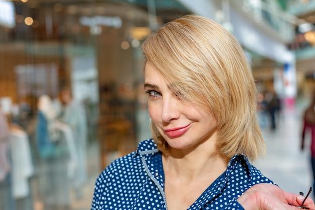 Ritratto di ragazza dello shopping di moda. donna di bellezza con i sacchetti della spesa nel centro commerciale. shopper. i saldi.