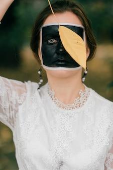 Ritratto di ragazza divertente con arte astratta faccia scuro che copre il suo occhio con una foglia gialla