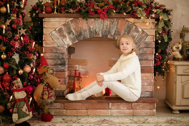 Ritratto di ragazza felice bambino biondo in maglione bianco ubicazione sul caminetto