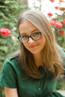 Ritratto di ragazza fiduciosa con gli occhiali, sorridente