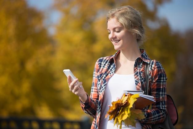 Ritratto di ragazza fuori studente, telefono cellulare in una mano