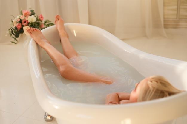 Ritratto di ragazza in un bagno con latte