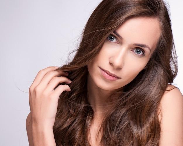 Ritratto di ragazza modello di moda con lunghi capelli che soffia.