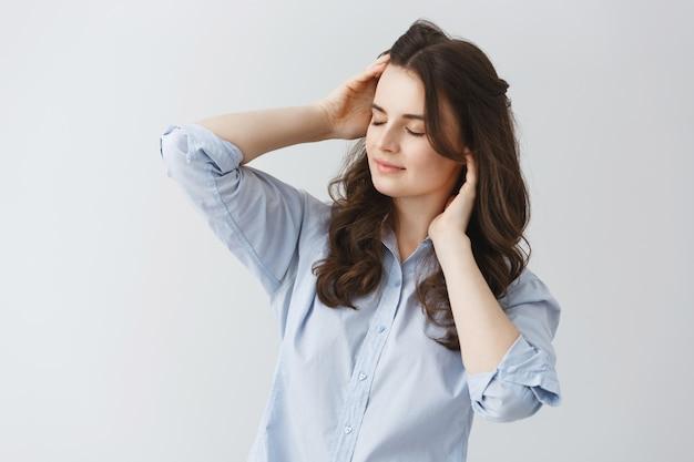 Ritratto di ragazza sexy con i capelli ondulati scuri e gli occhi chiusi, cercando di svegliarsi al mattino presto dopo due settimane di vacanza.