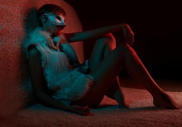 Ritratto di ragazza sexy in giacca di pelliccia che indossa maschera