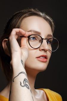 Ritratto di ragazza sospettosa con tatuaggio sul braccio.