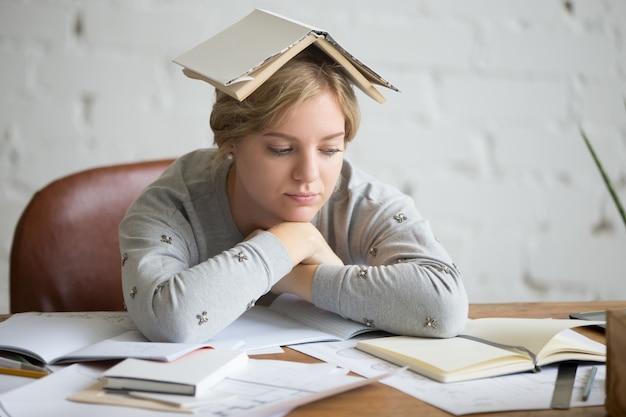 Ritratto di ragazza studente con libro aperto sulla sua testa