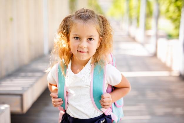 Ritratto di ragazzi delle scuole che corrono lungo la strada nel parco (focus sulla ragazza)