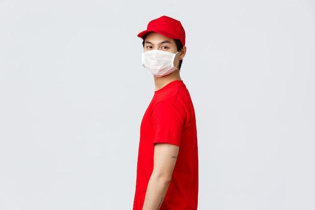 Ritratto di ragazzo asiatico consegna in berretto rosso e t-shirt, indossare maschera medica protettiva, girare il viso verso la telecamera. il corriere in uniforme consegna i pacchi mentre le persone restano al sicuro durante la quarantena covida