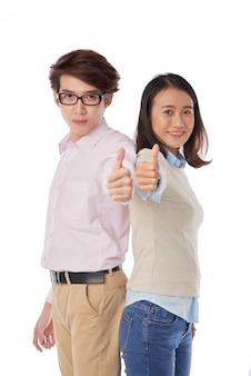 Ritratto di ragazzo asiatico e ragazza in piedi schiena contro schiena pollici in su