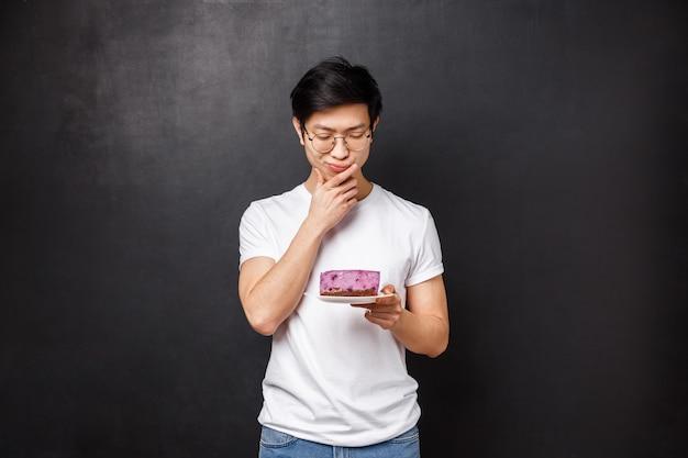 Ritratto di ragazzo asiatico riflessivo e dubbioso che sembra titubante al pezzo di torta, pensando di mangiarlo o lasciarlo in frigo, in piedi, a dieta, allergico agli ingridients