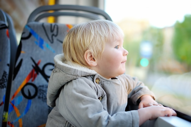 Ritratto di ragazzo carino bambino guardando fuori treno o finestra del tram
