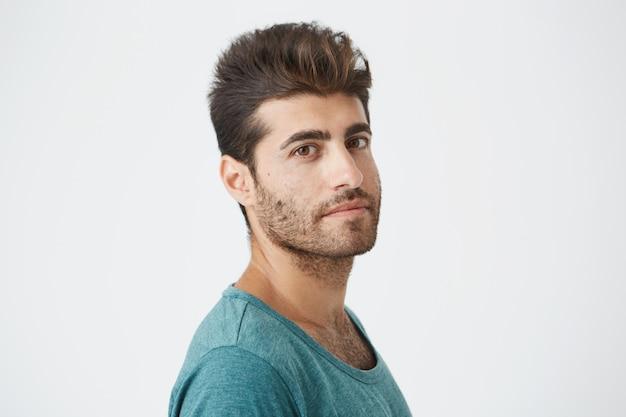 Ritratto di ragazzo caucasico maturo da vicino, in maglietta blu, con una buona acconciatura e barba che sorride leggermente in tre quarti. 3 4 ritratto da vicino.