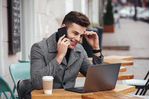 Ritratto di ragazzo contento che beve caffè da asporto in street cafe, lavorando con il notebook e avendo una piacevole conversazione mobile