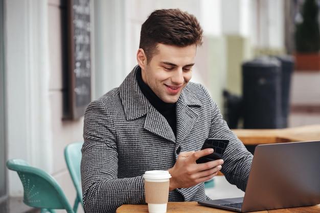 Ritratto di ragazzo di successo che riposa in street cafe, lavorando con il notebook e digitando il messaggio di testo sul suo telefono cellulare