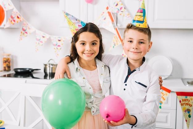 Ritratto di ragazzo e ragazza con palloncini in piedi in cucina