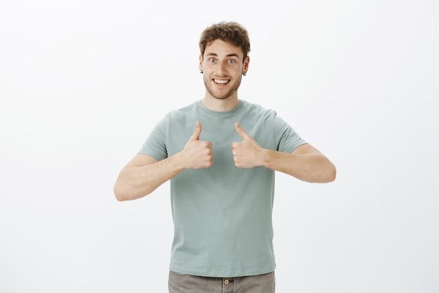 Ritratto di ragazzo europeo felice eccitato con capelli biondi in maglietta, mostrando i pollici in su e sorridendo ampiamente, essendo contento di ricevere un'idea eccellente