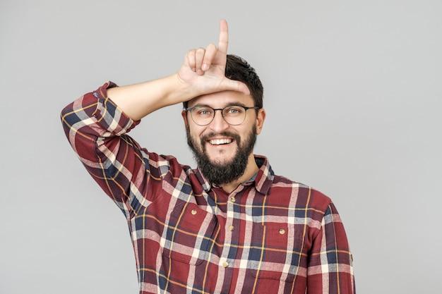 Ritratto di ragazzo felice con mostrando il segno del perdente