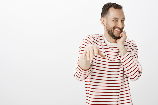 Ritratto di ragazzo gay carino compiaciuto impaziente in camicia a righe, arrossendo mentre l'uomo fa la proposta, ridacchiando dall'imbarazzo e timido, tirando il palmo per mettere l'anello al dito