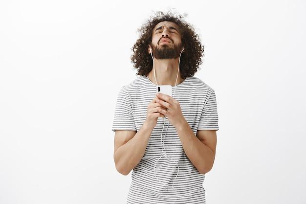 Ritratto di ragazzo ispanico contento bello gioioso con barba e capelli ricci, inclinando la testa all'indietro e chiudendo gli occhi mentre si ascolta la musica e si tiene lo smartphone