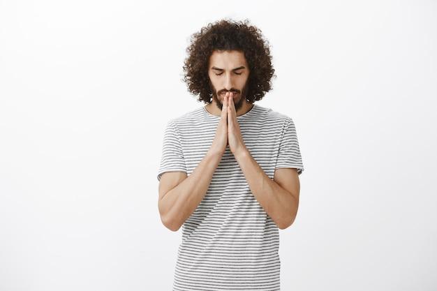 Ritratto di ragazzo ispanico credente concentrato con barba e acconciatura afro, chiudendo gli occhi, tenendo le mani in preghiera vicino alla bocca mentre si prega o si spera, parlando con dio
