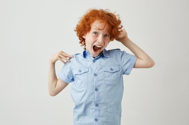 Ritratto di ragazzo pazzo di zenzero con i capelli ricci e le lentiggini che saltano, divertirsi con la bocca aperta e l'espressione del viso pazzo.