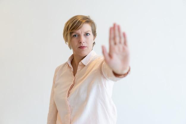 Ritratto di rigoroso metà degli adulti businesswoman facendo fermata gesto