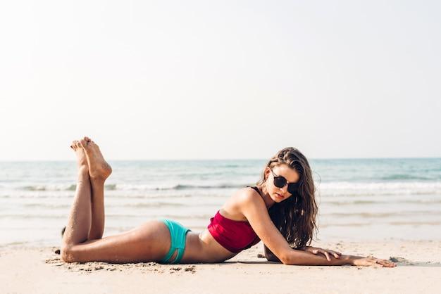 Ritratto di rilassamento sorridente della donna in bikini rosso sulla spiaggia tropicale vacanze estive
