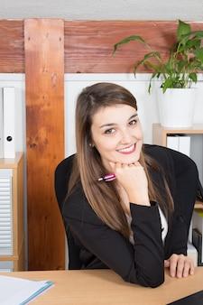 Ritratto di riuscita bella giovane imprenditrice seduto nel suo ufficio
