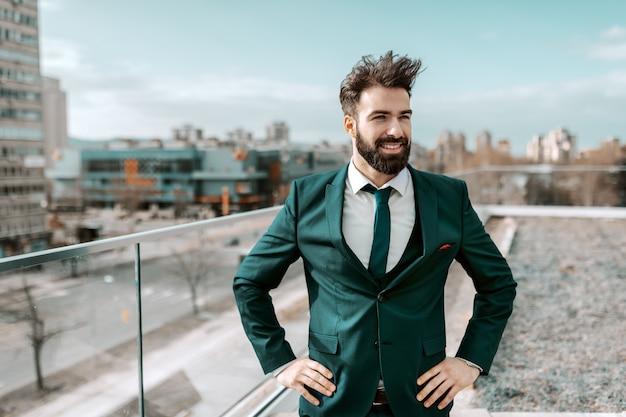 Ritratto di riuscito uomo d'affari sorridente nell'usura convenzionale che ha le mani sulle anche mentre stando sul tetto