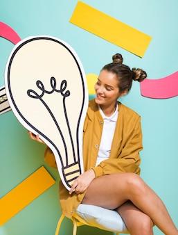 Ritratto di scolara con una grande lampadina