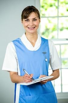 Ritratto di scrittura sorridente dell'infermiera sulla lavagna per appunti