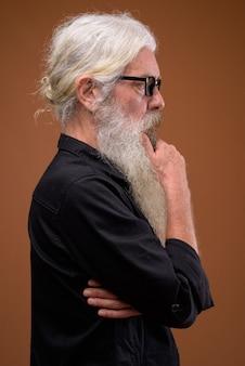 Ritratto di senior uomo barbuto vista di profilo mentre si pensa