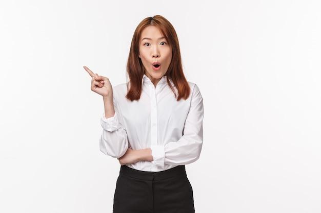 Ritratto di signora asiatica elegante divertita e curiosa in camicia bianca e gonna nera, diciamo wow e sorridente incuriosito mentre discute del nuovo prodotto in magazzino, qualcosa di interessante che punta a sinistra,
