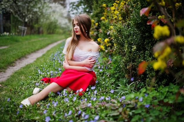Ritratto di sitiing bella ragazza con le labbra rosse al giardino di fiori di primavera su erba con fiori, indossare abito rosso e camicetta bianca.