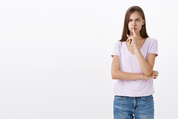 Ritratto di sorella prepotente infastidita e severa dall'aspetto serio in abito casual accigliata che zittisce con il dito indice sulla bocca che vieta di parlare laud o di dire il segreto