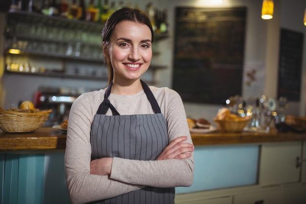 Ritratto di sorridente cameriera in piedi al banco