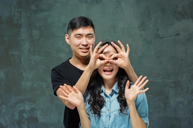 Ritratto di sorridente coppia coreana su un grigio