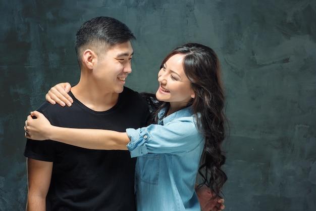 Ritratto di sorridente coppia coreana su uno sfondo grigio studio