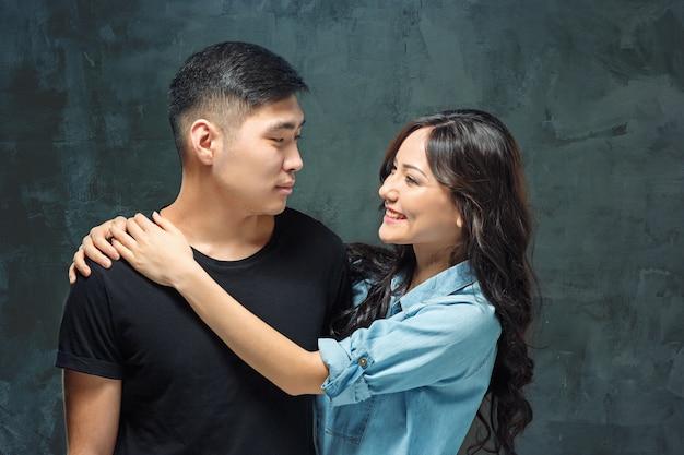 Ritratto di sorridente coppia coreana su uno studio grigio