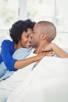 Ritratto di sorridente coppia sul divano a guardare l'altro