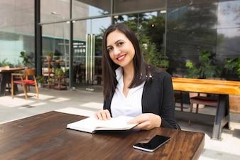 Ritratto di sorridente giovane imprenditrice o studente al caffè