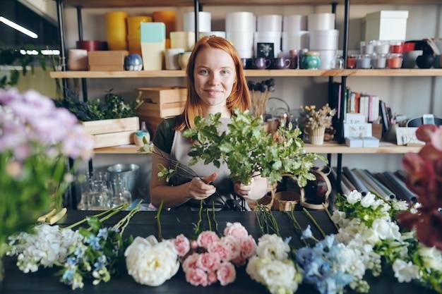 Ritratto di sorridente ragazza attraente rossa in grembiule in piedi al tavolo con i fiori in fila e l'aggiunta di rami verdi al bouquet