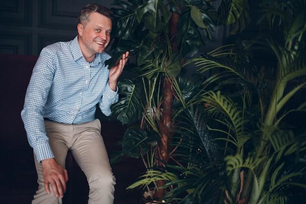 Ritratto di sorridente senior adulto medio uomo in camicia blu tenendo la foglia verde pianta guardando la fotocamera. piante da giardinaggio domestiche.