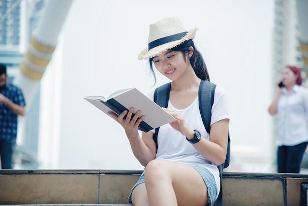 Ritratto di sorridere della ragazza del giovane studente che lavora e che impara sul computer portatile