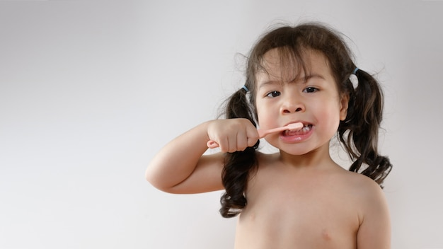 Ritratto di spazzolatura sorridente dei denti della piccola ragazza asiatica riccia. ragazza del bambino che sorride mentre lavandosi i denti. sanità, igiene dentale