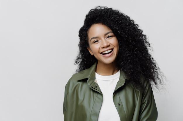 Ritratto di spensierata gioiosa signora afroamericana con un sorriso raggiante